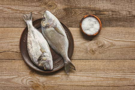 top view of salt and plate with uncooked fish on wooden table Stock Photo