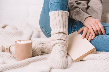 cropped shot of girl in knitted socks sitting with book on warm blanket Фото со стока