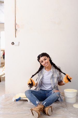 beautiful african american woman posing and looking at camera during renovation of new home