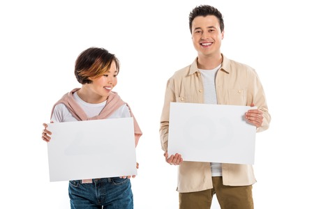 cheerful husband and wife looking at camera and holding two blank boards isolated on white