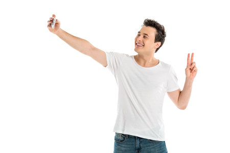 handsome smiling man taking selfie on smartphone and showing peace sign isolated on white