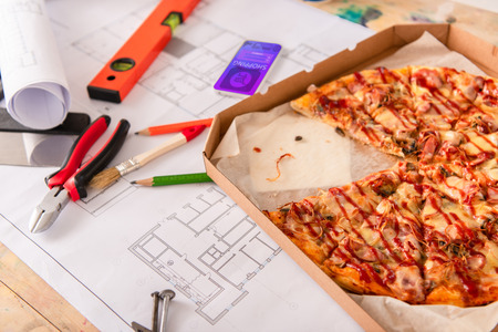 close-up shot of box with pizza, tools and smartphone with shopping app on screen on building plan