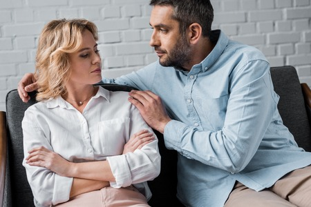 man talking to wife while sitting on couch after quarrel Stock Photo