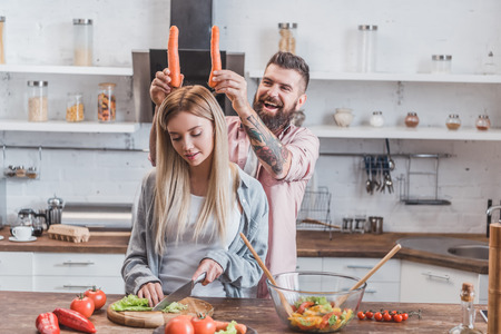 funny man putting carrots on woman head while girl cooking dinner Imagens