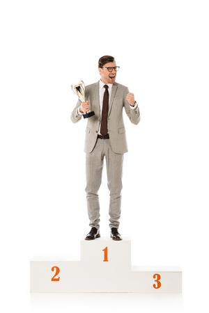 hübscher aufgeregter Geschäftsmann mit Trophäenpokal, der auf dem Siegerpodest steht, isoliert auf weiß