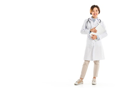 smiling female doctor looking at camera, standing and holding diagnosis isolated on white