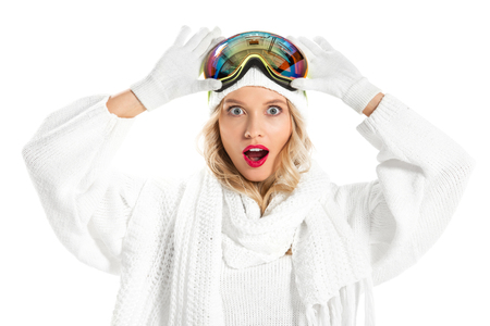 Surprised young woman holding ski goggles on head and looking at camera isolated on white