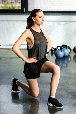 beautiful athletic sportswoman doing lunge exercise at gym