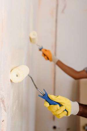 cropped image of couple painting wall by paint rollers at new home Imagens