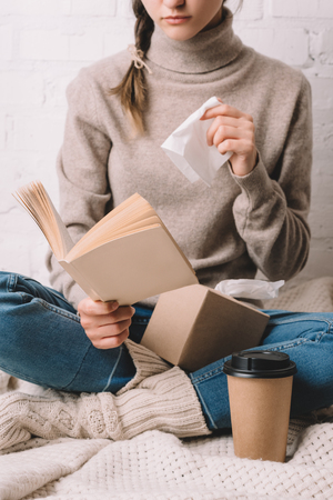 cropped shot of woman holding paper tissue and reading book Stok Fotoğraf