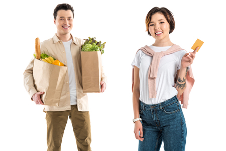 smiling husband holding grocery bag while wife presenting credit card isolated on white