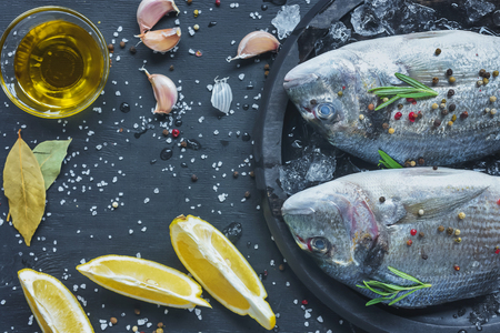 elevated view of raw fish covered by pepper and rosemary in tray on black table