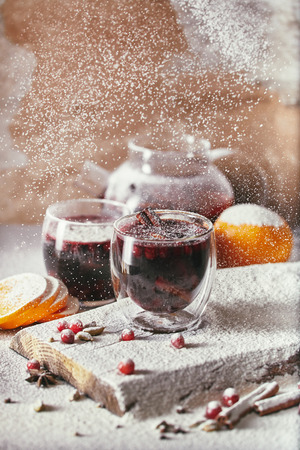 powdered sugar falling on two glasses of tasty mulled wine with cranberries on table in kitchen Stock Photo