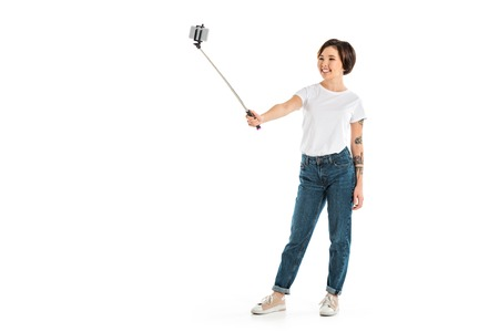 beautiful young woman taking selfie on smartphone using selfie stick isolated on white