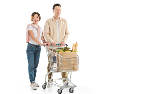 happy young couple with shopping cart full of groceries looking at camera isolated on white