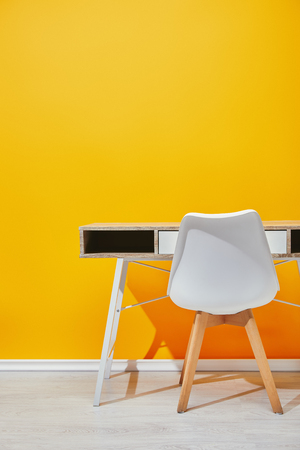Wooden table with white chair naer yellow wall Stock Photo