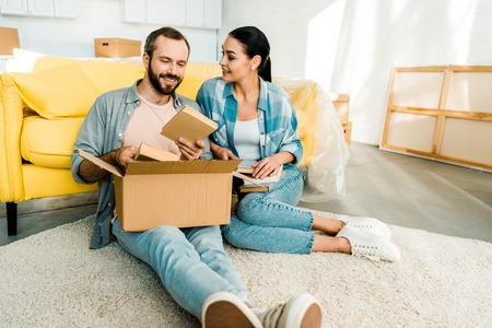 happy couple putting books in cardboard box while packing for new house, moving concept