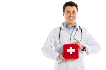 handsome male doctor holding first aid kit and looking at camera isolated on white