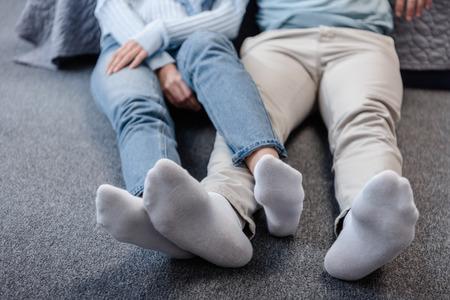 Ausgeschnittene Ansicht eines Paares, das mit gekreuzten Beinen auf dem Boden sitzt Standard-Bild