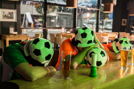 Football fans napping on wooden bar counter