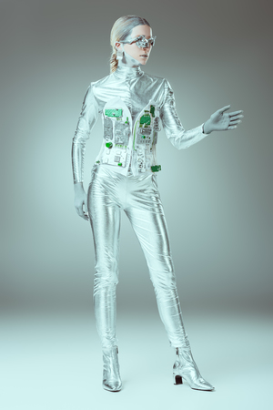 full length view of silver woman robot standing on grey, future technology concept