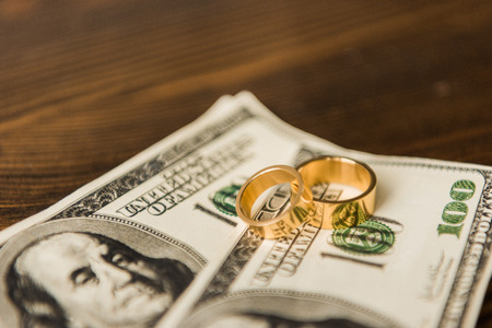close-up shot of cash and wedding rings on wooden table Stock Photo