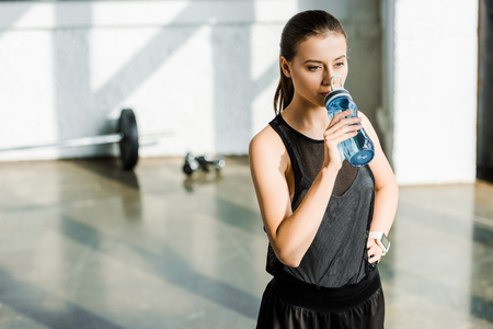 beautiful concentrated sportswoman drinking water from sport bottle at gym 版權商用圖片