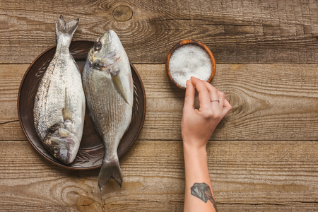 cropped image of tattooed woman salting uncooked fish on wooden table Stock Photo