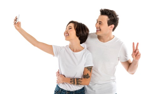 smiling couple taking selfie on smartphone and showing peace sign isolated on white Stok Fotoğraf