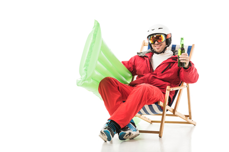 man in ski clothes with beer bottle and pool mattress sitting in deck chair and smiling isolated on white