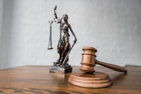 close-up shot of judge gavel and themis statue on wooden table