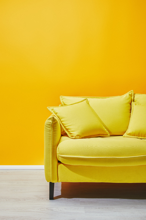 Sofa with pillows near bright yellow wall