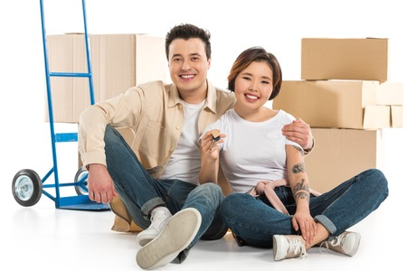 couple hugging and holding keys with cardboard boxes on background, moving to new house concept