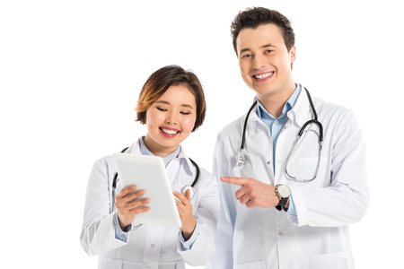 smiling female and male doctors using digital tablet isolated on white