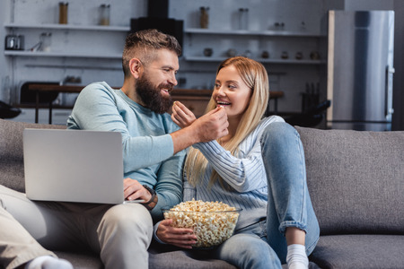 Husband and wife sitting on sofa and sharing food
