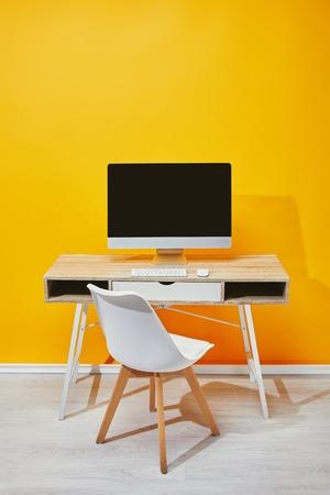 Computadora en el lugar de trabajo con silla y pared amarilla al fondo