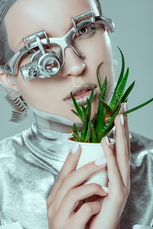 silver robot touching face with potted plant isolated on grey, future technology concept