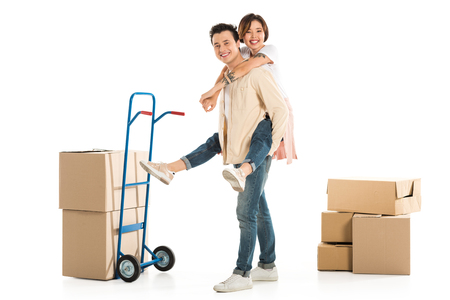 husband giving piggyback ride to wife near cardboard boxes and hand truck on background, moving to new house concept Stok Fotoğraf