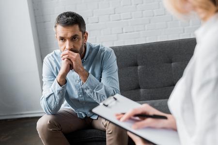 사무실에서 심리학자 치료 세션에 우울한 성인 남자 스톡 콘텐츠