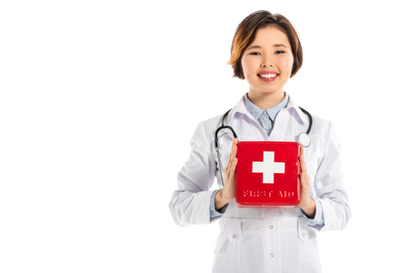 smiling female doctor isolated on white holding first aid kit and looking at camera