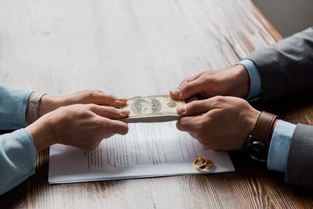 Vista parcial del abogado y el cliente sosteniendo billetes de dólar por encima del decreto de divorcio con anillos de boda