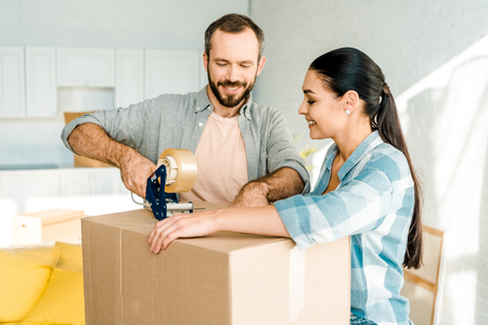 handsome husband and wife packing cardboard box with scotch tape, moving concept
