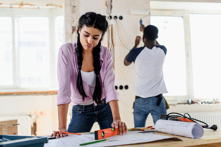 pensive young woman with spirit level looking at blueprint while her boyfriend working behind during renovation of home Stock Photo