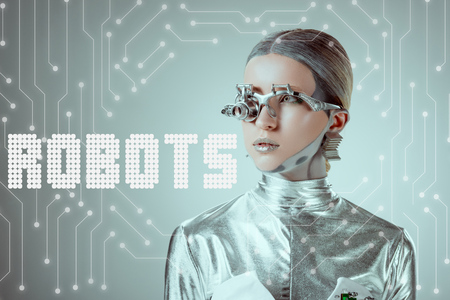 futuristic silver cyborg looking away isolated on grey with