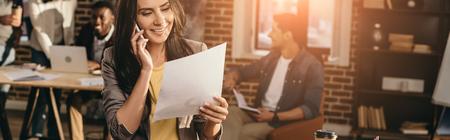 Ausgeschnittene Ansicht einer Gelegenheitsgeschäftsfrau, die im Loft-Büro mit Kollegen und hinterleuchteter Hintergrundbeleuchtung auf dem Smartphone arbeitet und spricht