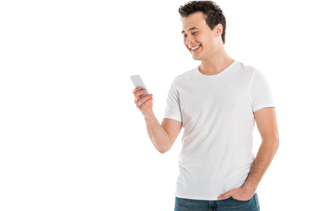cheerful handsome man using smartphone isolated on white