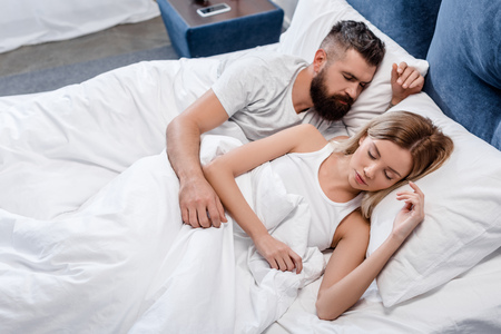 Young couple sleeping in bright bedroom in morning