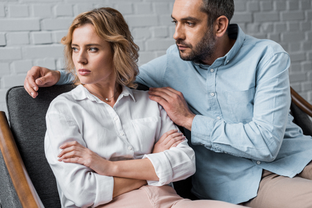 man talking to depressed wife while sitting on couch after argument 版權商用圖片