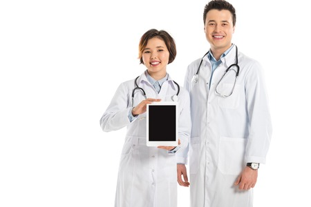 female and male doctors presenting digital tablet with blank screen and looking at camera isolated on white