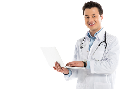 smiling male doctor holding laptop and looking at camera isolated on white